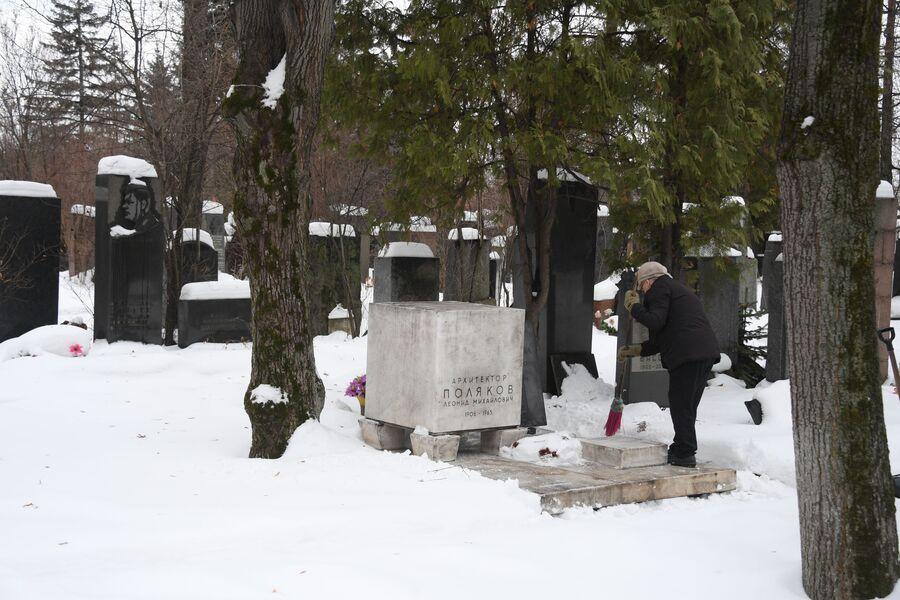 Женщина очищает от снега могилу архитектора Леонида Полякова
