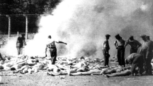 Члены зондеркоманды сжигают тела убитых газом заключенных Освенцима