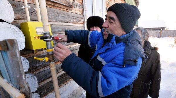 Техник газовой службы подключает газ в жилой дом