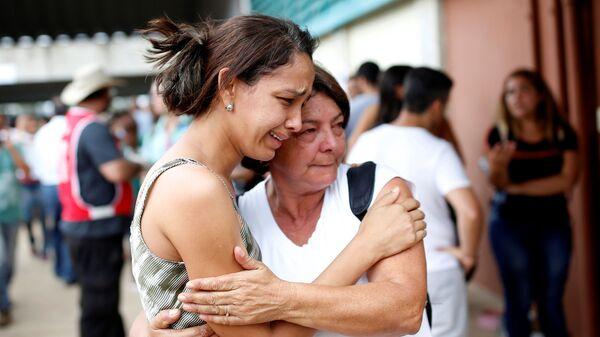 Родственники пропавших людей во время прорыва плотин на шахте корпорации Vale в муниципалитете Брумадинью в Бразилии