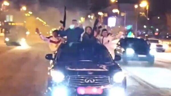 Стоп-кадр видеозаписи, на которой молодые люди едут с оружием по улицам Тюмени