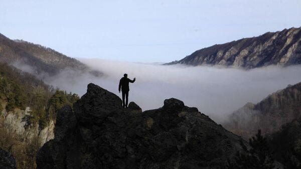 Турист фотографирует туман в ущелье горного склона Галанчожского района Чеченской республики