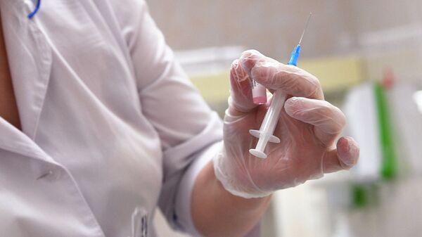 Медицинская сестра готовит шприц для прививки от кори в детской поликлинике