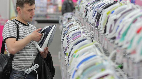 Покупатель выбирает утюг в магазине бытовой техники и электроники