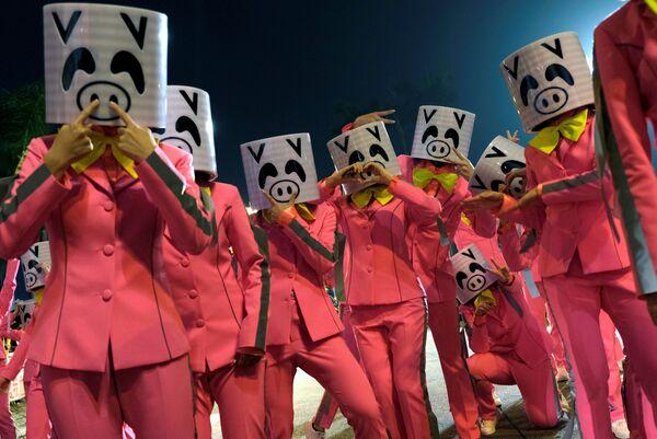 Участники парада в масках свиней во время Лунного Нового года в Гонконге