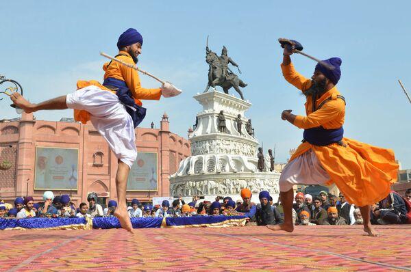 Индийские сикхи демонстрируют приемы боевого искусства Гатка во время соревнования в Амритсаре