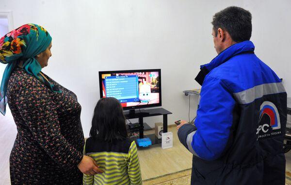 Инженер настраивает приставку цифрового телевидения в одном из жилых домов в Гудермесе