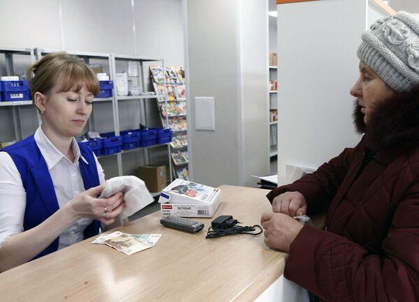 Оператор отделения почтовой связи в городе Гаврилов Ям упаковывает купленную жительницей города приставку для цифрового эфирного телевидения