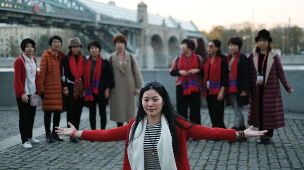 Туристы на Пушкинской набережной в Москве. На дальнем плане: Андреевский мост