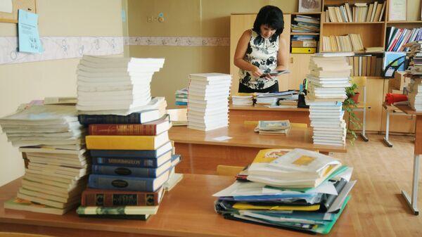 Учительница сортирует учебники в классе. Архивное фото
