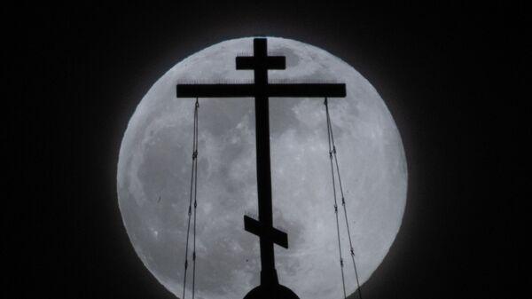 Православный крест в Москве на фоне луны