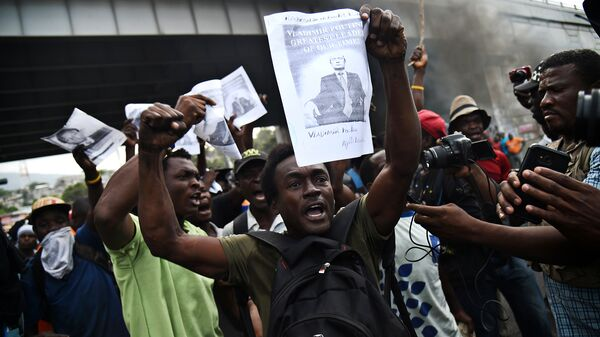 Участник акции протеста с портретом Владимира Путина в столице Гаити Порт-о-Пренсе. 15 февраля 2019