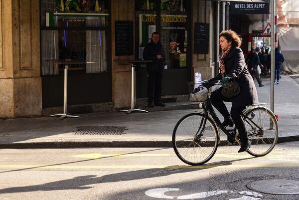 Женщина едет на велосипеде по одной из улиц Женевы