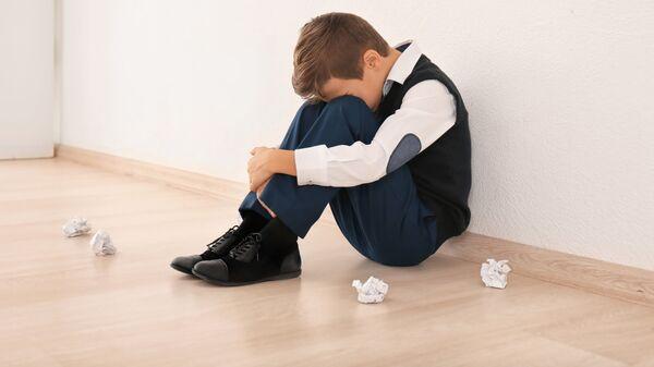 Расстроенный ребенок сидит на полу в школе