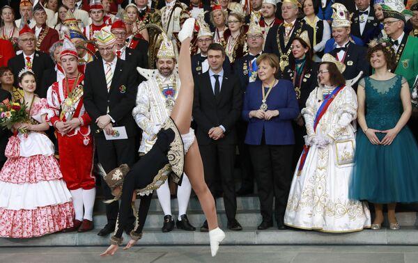 Канцлер Германии Ангела Меркель наблюдает за выступлением танцоров во время приема в Канцелярии в Берлине