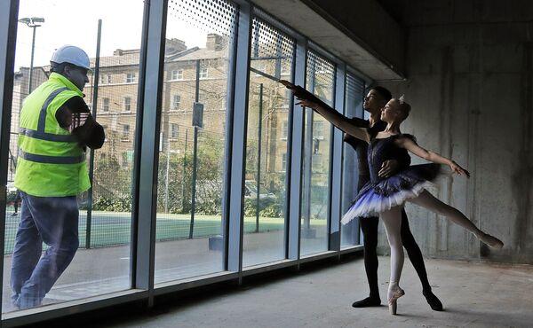 Рабочий наблюдает за фотосессией артистов балета Брандона Бреретони Эмил Пол в Лондоне