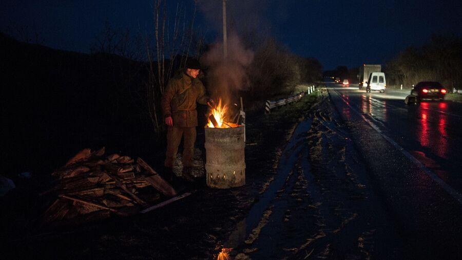 Местный житель из отряда самообороны греется у огня на блокпосту возле Севастополя