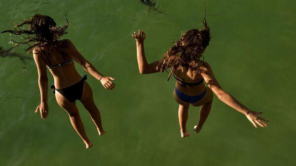 Девушки прыгают в море на пляже la concha, Испания