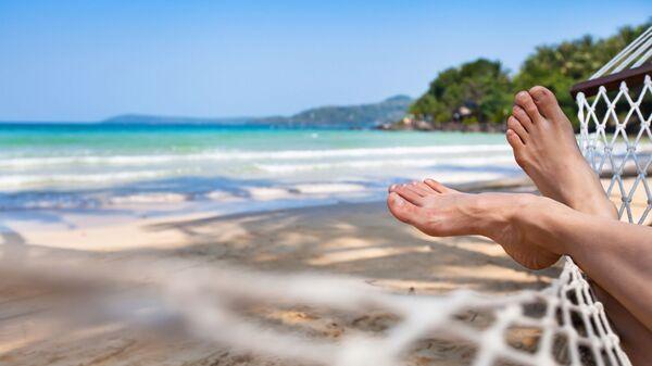 Девушка отдыхает в гамаке на пляже