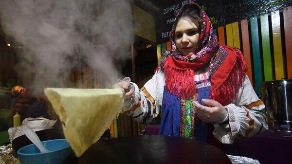 Девушка печет блины во время празднования Масленицы