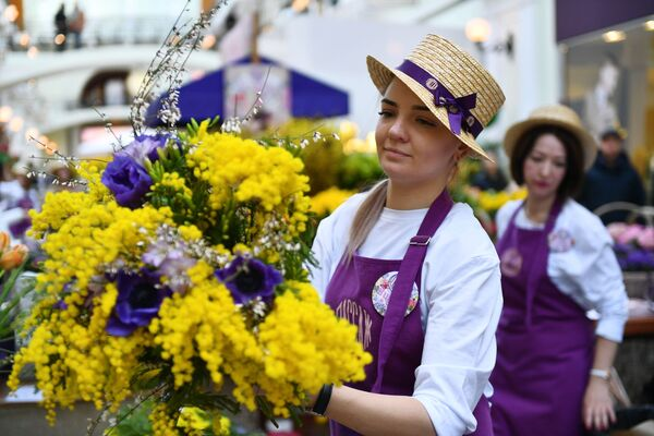Продажа мимозы на Весеннем цветочном базаре в Петровском Пассаже в Москве