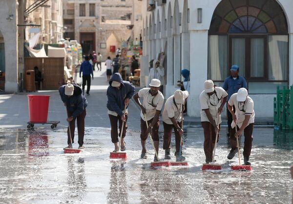 Мужчины моют одну из улиц в городе Доха