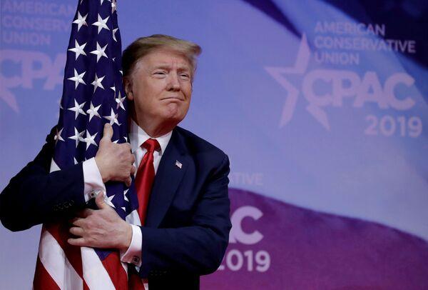 Президент США Дональд Трамп обнимает американский флаг