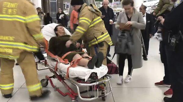 В аэропорту имени Джона Кеннеди медицинский персонал сопровождает пассажира, пострадавшего от турбулентности во время рейса Турецких авиалиний из Стамбула в Нью-Йорк. 9 марта 2019