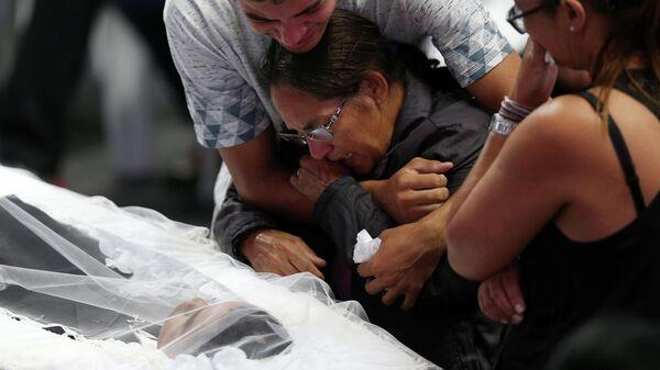 Одна из жертв стрельбы в школе Бразилии во время коллективной церемонии похорон. 14 марта 2014