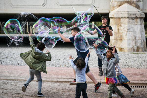 Дети играют с гигантскими мыльными пузырями возле моста Анхель Кустодио в парке, находящемся на месте старого русла реки Турии в Валенсии