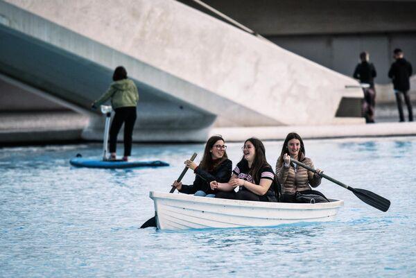 Туристы катаются на лодке в бассейне на территории архитектурного комплекса Город Науки и Искусств в Валенсии