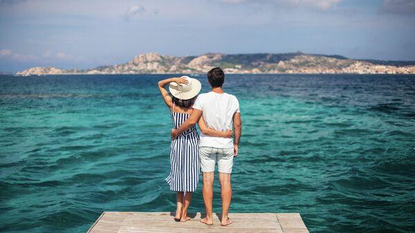 Молодая пара на пирсе на Сардинии