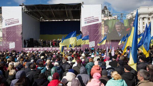 Люди слушают предвыборную речь президента Украины Петра Порошенко на Михайловской площади в Киеве. 17 марта 2019