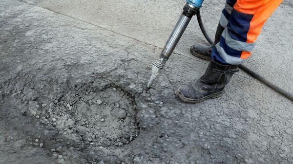 Рабочий бригады ГБУ Автомобильные дороги демонтирует старое дорожное полотно пневматическим отбойным молотком