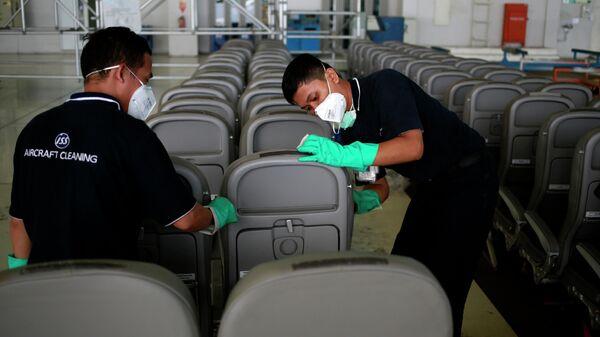 Работники клининговой компании моют сиденья в ангаре международного аэропорта Сукарно Хатта, Индонезия