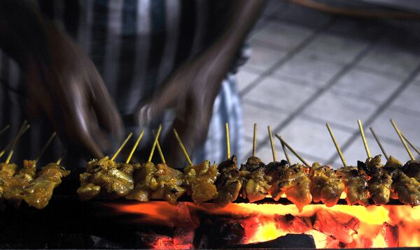 Продавец готовит сате на рынке в Куала-Лумпуре