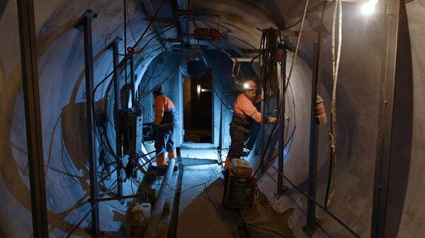 Рабочие проводят строительно-монтажные работы в тоннеле кабельного коллектора