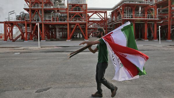 Мужчина с флагами Ирана на заводе по переработке природного газа