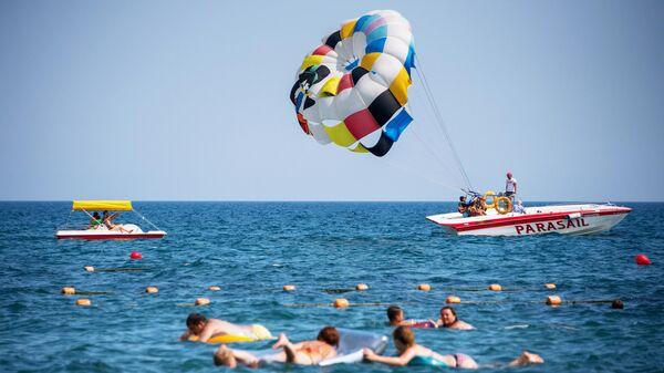 Туристы занимаются парасейлингом на пляже в Судаке