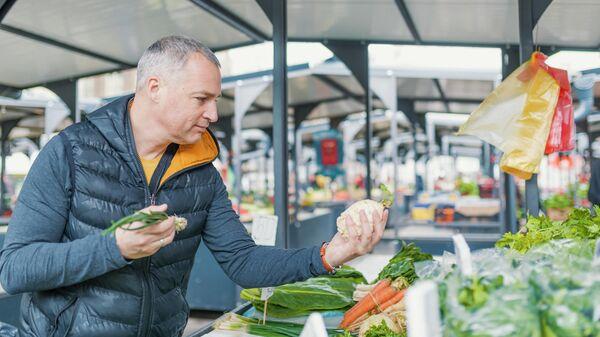 Мужчина выбирает овощи на рынке