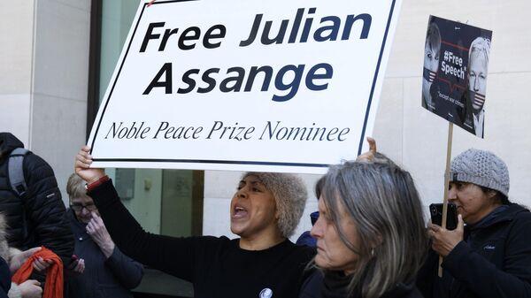 Люди стоят с табличками Освободить Джулиана Ассанжа у Вестминстерского суда в Лондоне