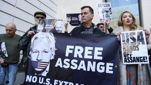 Люди стоят с баннерами Освободить Джулиана Ассанжа у Вестминстерского суда в Лондоне. Архивное фото