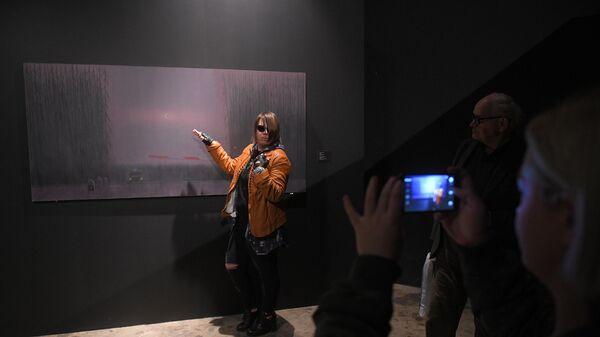 Девушка позирует на фоне картины Александра Якута на выставке Неон в Музее Москвы