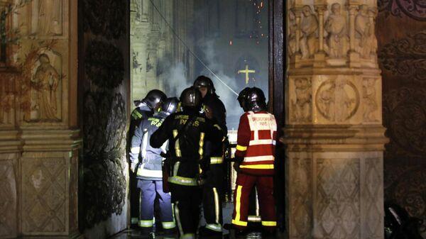 Пожарные у входа в собор Парижской Богоматери во время пожара