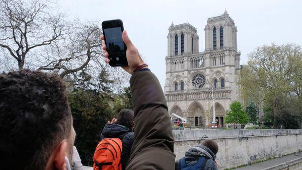 Прохожий фотографирует собор Парижской Богоматери после пожара