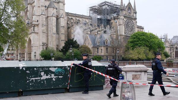 Сотрудники полиции огораживают территорию у собора Парижской Богоматери после пожара