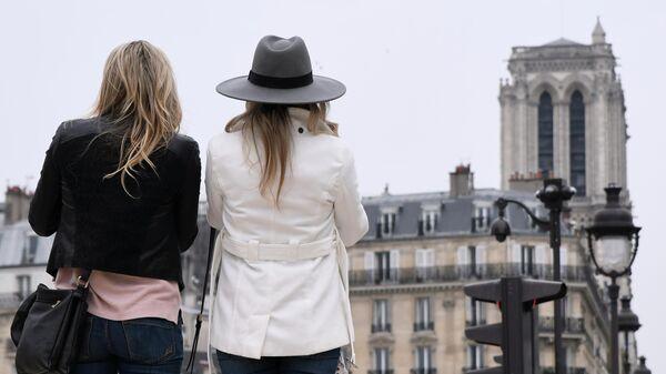 Девушки смотрят на башню собора Парижской Богоматери после пожара