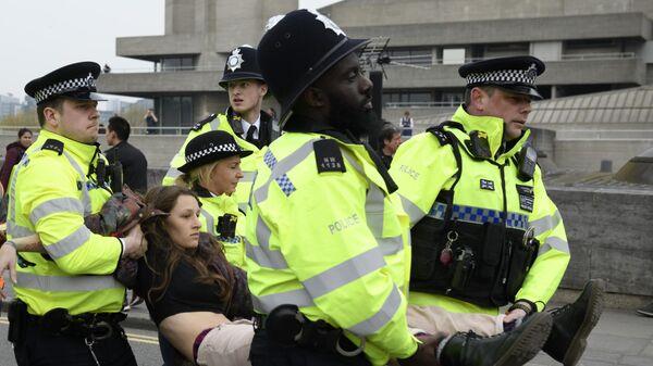 Сотрудники полиции задерживают участницу акции протеста против загрязнения окружающей среды, проходящей в Лондоне