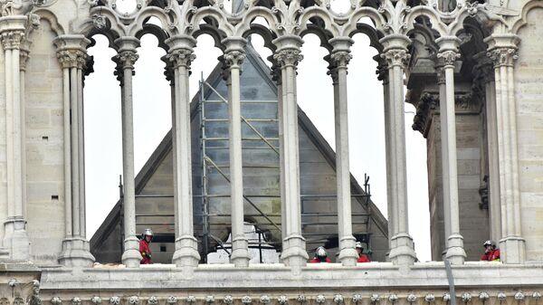 Пожарные осматривают крышу собора Парижской Богоматери после пожара