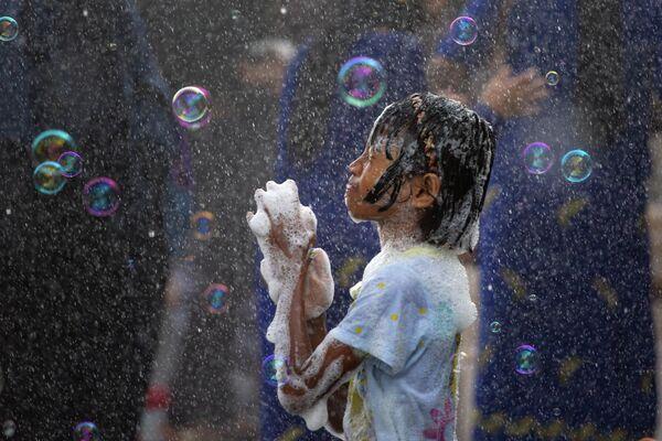 Ребенок во время празднования буддистского Нового года в Янгоне, Мьянма